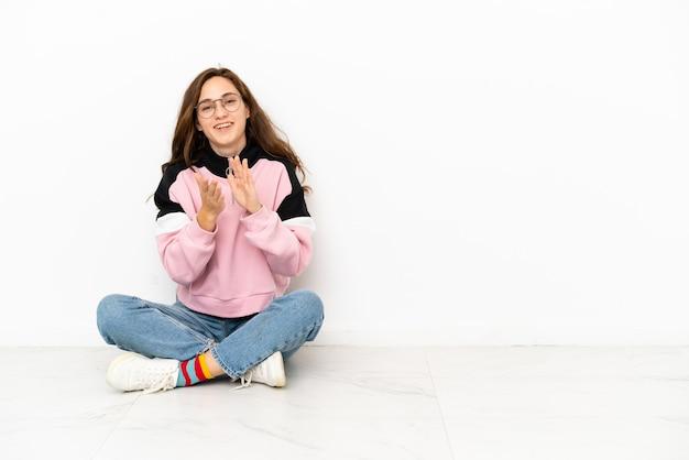 Jeune femme de race blanche assise sur le sol isolé sur fond blanc applaudissant après présentation lors d'une conférence