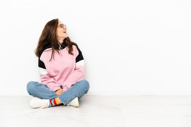 Jeune femme de race blanche assise sur le sol isolé sur fond blanc en riant en position latérale