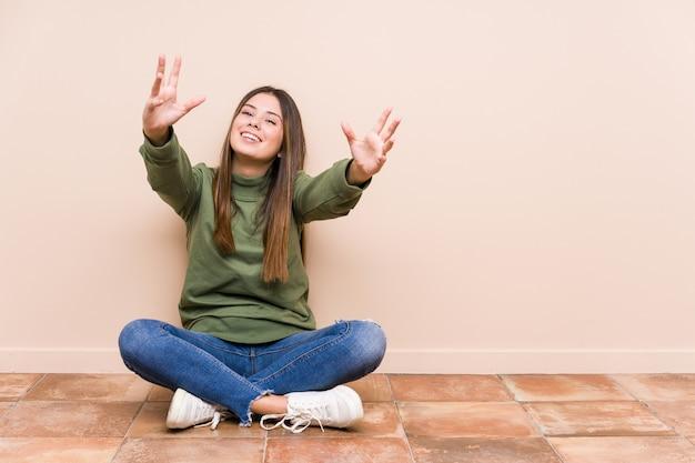 Jeune femme de race blanche assise sur le sol isolé se sent confiant en donnant un câlin