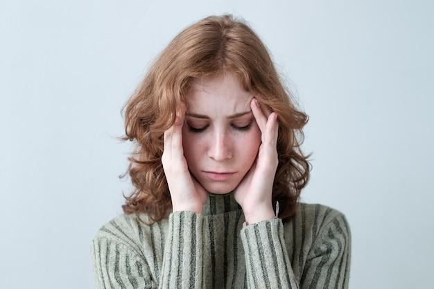 Jeune femme de race blanche aux cheveux bouclés rouges tenant la tête étant dans la douleur