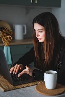 Jeune femme de race blanche aux cheveux brune utilise un ordinateur portable dans la cuisine à la maison, en tapant du texte sur le clavier