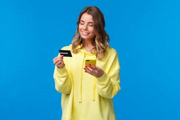 Jeune femme de race blanche aux cheveux courts blonds à l'aide de téléphone portable et insérer les numéros de carte de crédit pour payer son achat en ligne, faire du shopping dans la boutique internet, sourire heureux