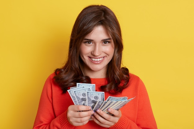 Jeune femme de race blanche aux cheveux noirs debout contre le mur jaune avec un éventail d'argent dans les mains, la dame gagne à la loterie, ayant une récompense, gagnant un gros sac d'argent, avec un sourire heureux.
