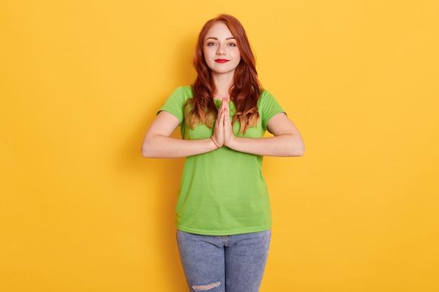 Jeune femme de race blanche aux taches de rousseur rousse posant avec les mains pressées ensemble, posant isolé sur un mur jaune, ayant concentré une expression calme sur son visage.