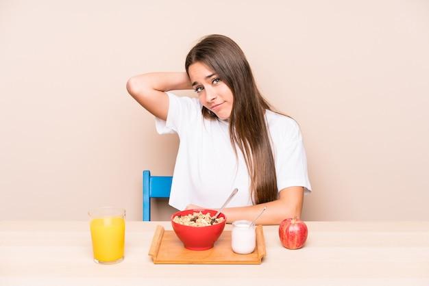 Jeune femme de race blanche ayant un petit déjeuner touchant l'arrière de la tête, pensant et faisant un choix.