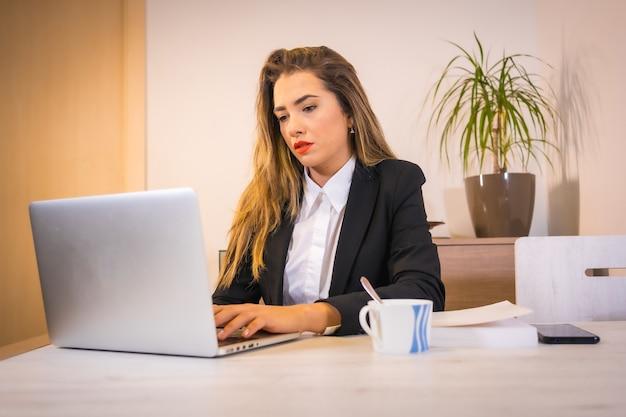 Jeune femme de race blanche blonde avec un café travaillant avec l'ordinateur