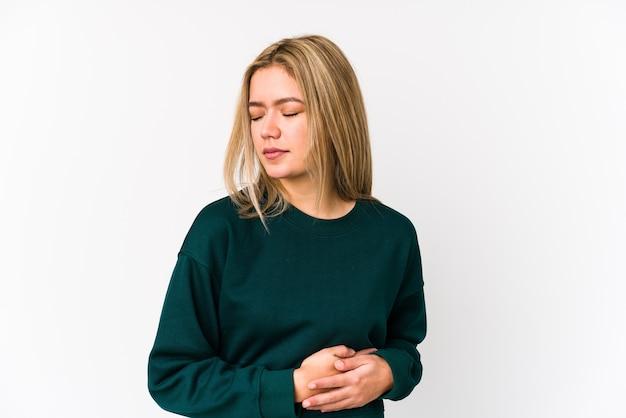 Jeune femme de race blanche blonde isolée ayant une douleur au foie, mal d'estomac.
