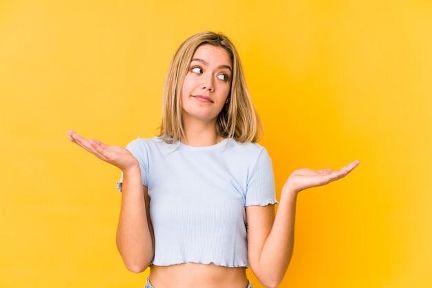 Jeune femme de race blanche blonde isolée sur fond jaune en doutant et en haussant les épaules dans le geste d'interrogation.
