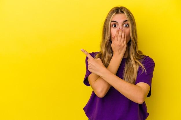 Jeune femme de race blanche blonde isolée sur fond jaune pointant vers le côté