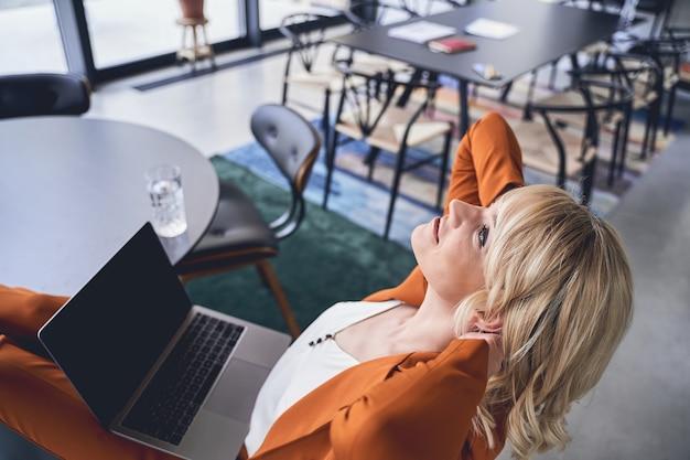 Jeune femme de race blanche blonde sereine avec ses mains derrière sa tête, assise au bureau