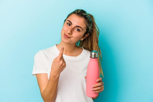 Jeune femme de race blanche blonde tenant un thermo isolé sur fond bleu pointant avec le doigt sur vous comme si vous invitiez à vous rapprocher.