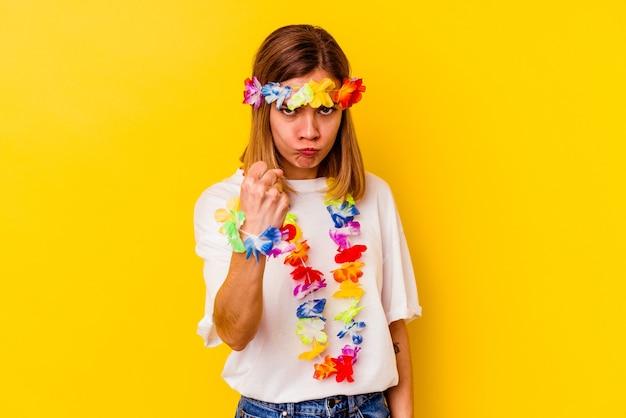 Jeune femme de race blanche célébrant une fête hawaïenne isolée sur fond jaune montrant le poing à la caméra, expression faciale agressive.