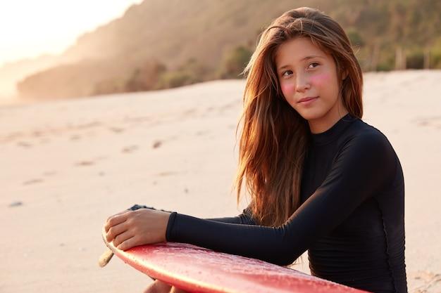 Jeune femme de race blanche contemplative aux cheveux longs, surfez sur le zinc sur les joues