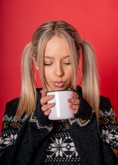 Jeune femme de race blanche dans un joli pull de boire du thé assis contre un mur rouge