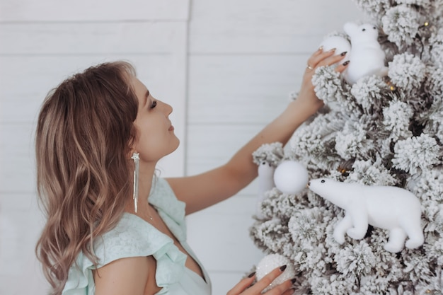 Une jeune femme de race blanche dans une robe de fête bleue décore l'arbre de noël avec des jouets blancs