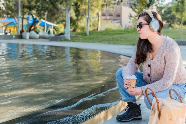 Jeune femme de race blanche écoutant de la musique avec des écouteurs tout en buvant du café dans un parc