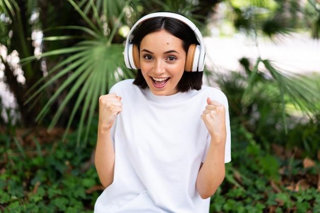 Jeune femme de race blanche avec des écouteurs à l'extérieur pour célébrer une victoire en position de vainqueur