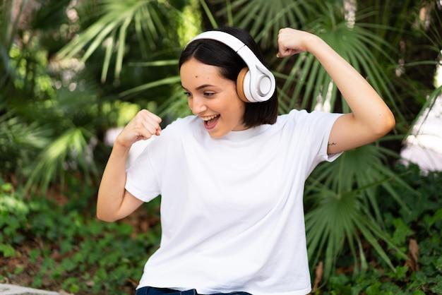 Jeune femme de race blanche avec des écouteurs à l'extérieur pour célébrer une victoire