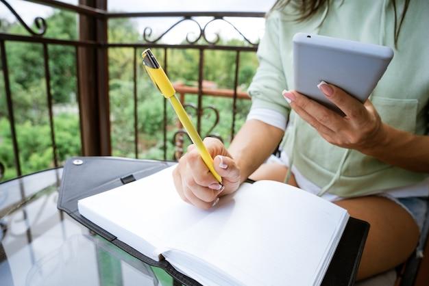 Jeune femme de race blanche écrit dans un cahier avec un stylo dans des vêtements décontractés avec un téléphone à la main sur un balcon d'été