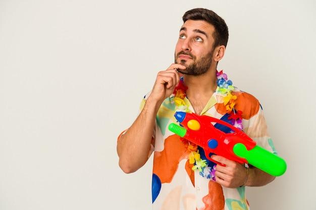 Jeune femme de race blanche sur une fête hawaïenne tenant un pistolet à eau isolé sur fond blanc à la recherche de côté avec une expression douteuse et sceptique.
