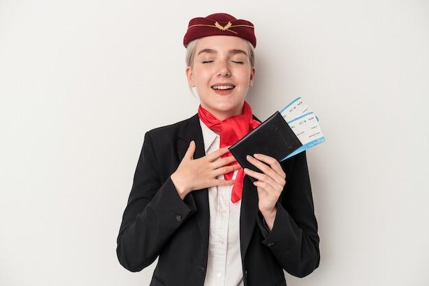 Jeune femme de race blanche hôtesse de l'air tenant un passeport isolé sur fond blanc rit fort en gardant la main sur la poitrine.