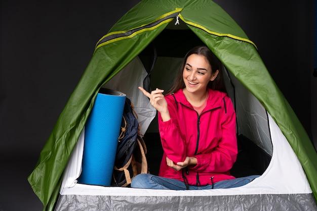 Jeune femme de race blanche à l'intérieur d'une tente verte camping doigt pointé sur le côté