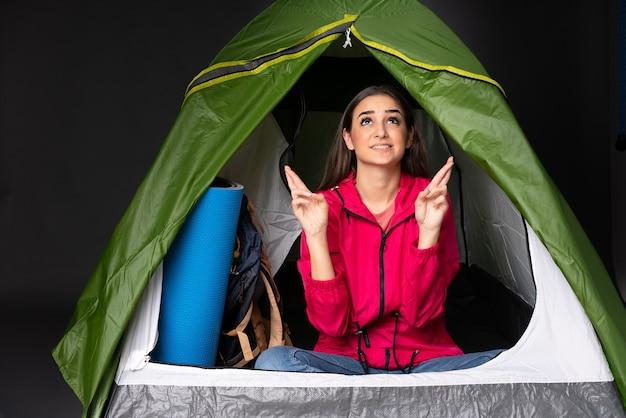 Jeune femme de race blanche à l'intérieur d'une tente verte de camping