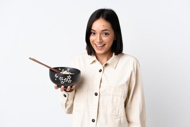 Jeune femme de race blanche isolée sur blanc avec surprise et expression du visage choqué tout en tenant un bol de nouilles avec des baguettes