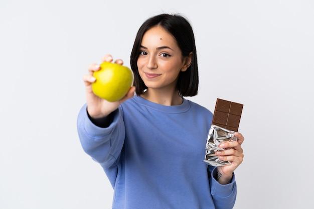 Jeune femme de race blanche isolée sur fond blanc en prenant une tablette de chocolat dans une main et une pomme dans l'autre
