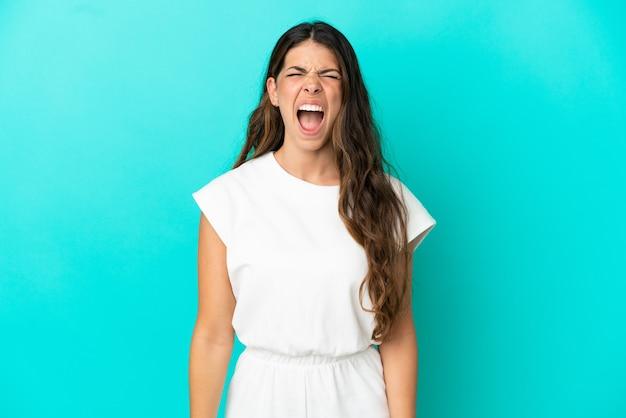 Jeune femme de race blanche isolée sur fond bleu criant à l'avant avec la bouche grande ouverte
