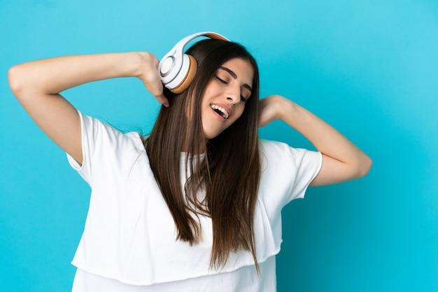 Jeune femme de race blanche isolée sur fond bleu, écouter de la musique
