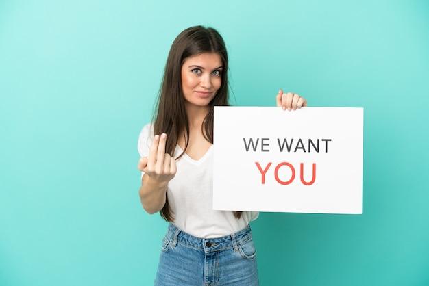 Jeune femme de race blanche isolée sur fond bleu tenant le panneau we want you et faisant le geste à venir