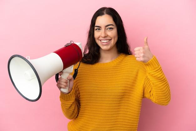Jeune femme de race blanche isolée sur fond rose tenant un mégaphone avec le pouce vers le haut