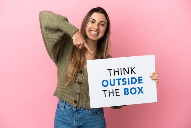 Jeune femme de race blanche isolée sur fond rose tenant une pancarte avec du texte think outside the box et le pointant