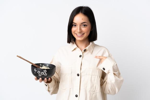 Jeune femme de race blanche isolée sur un mur blanc avec une expression faciale surprise tout en tenant un bol de nouilles avec des baguettes