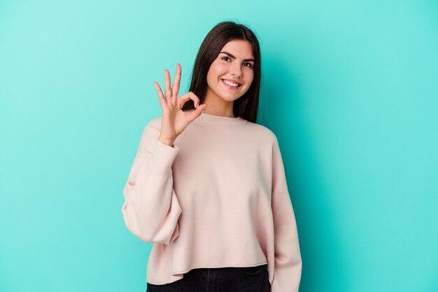 Jeune femme de race blanche isolée sur un mur bleu joyeux et confiant montrant le geste ok
