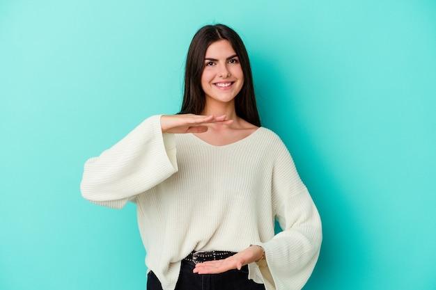 Jeune femme de race blanche isolée sur un mur bleu tenant quelque chose à deux mains, présentation du produit