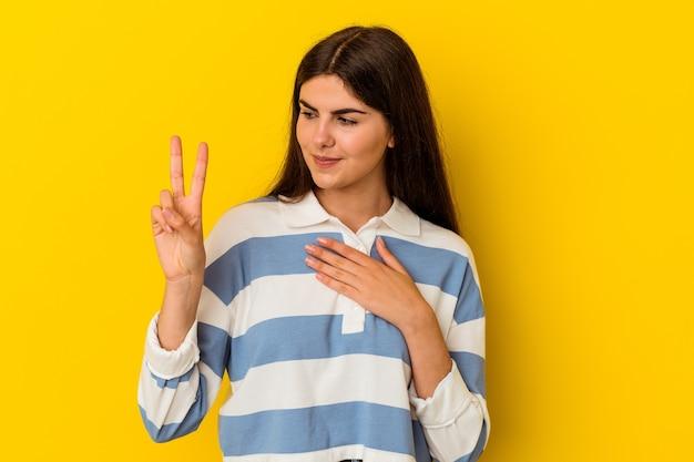 Jeune femme de race blanche isolée sur un mur jaune en prêtant serment, mettant la main sur la poitrine