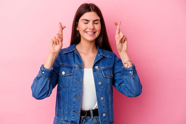 Jeune femme de race blanche isolée sur le mur rose croisant les doigts pour avoir de la chance