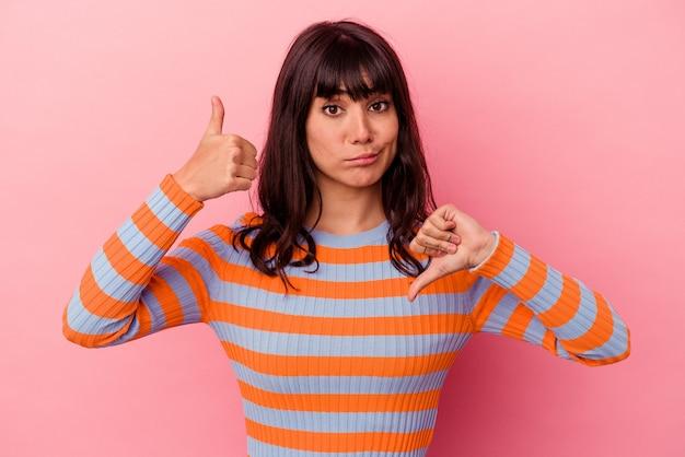 Jeune femme de race blanche isolée sur un mur rose montrant les pouces vers le haut et les pouces vers le bas, difficile de choisir le concept