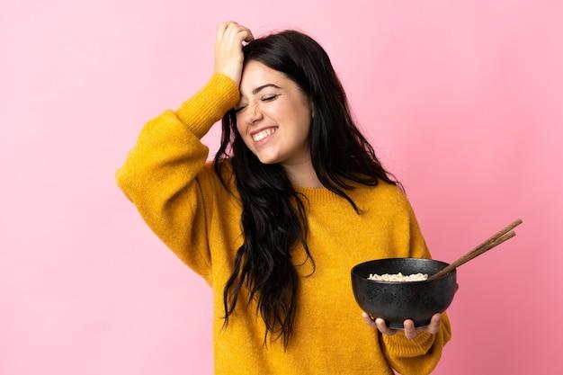 Jeune femme de race blanche isolée sur un mur rose a réalisé quelque chose et l'intention de la solution tout en tenant un bol de nouilles avec des baguettes