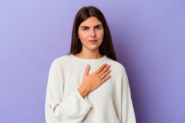 Jeune femme de race blanche isolée sur un mur violet en prêtant serment, mettant la main sur la poitrine