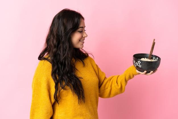 Jeune femme de race blanche isolée sur rose avec une expression heureuse tout en tenant un bol de nouilles avec des baguettes