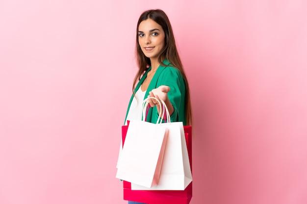 Jeune femme de race blanche isolée sur rose tenant des sacs à provisions et de les donner à quelqu'un