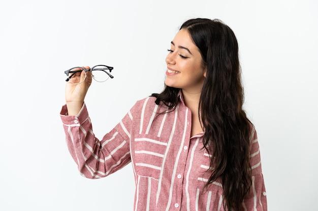 Jeune femme de race blanche avec des lunettes isolé sur fond blanc avec une expression heureuse