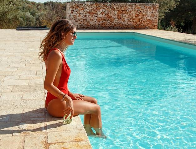 Jeune femme de race blanche en maillot de bain rouge avec cocktail tropical se détendre près d'une piscine