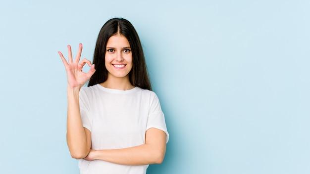 Jeune femme de race blanche sur le mur bleu clignote un œil et détient un geste correct avec la main.
