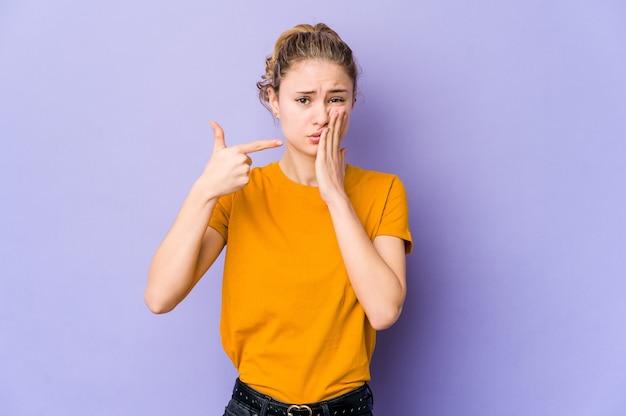 Jeune femme de race blanche sur un mur violet ayant une forte douleur aux dents, mal molaire.