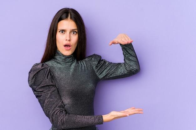 Jeune femme de race blanche sur le mur violet choqué et étonné tenant un espace vide entre les mains.