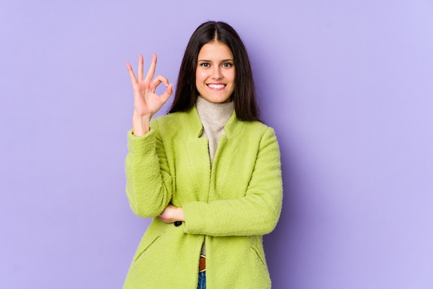 Jeune femme de race blanche sur le mur violet fait un clin d'œil et détient un geste correct avec la main.